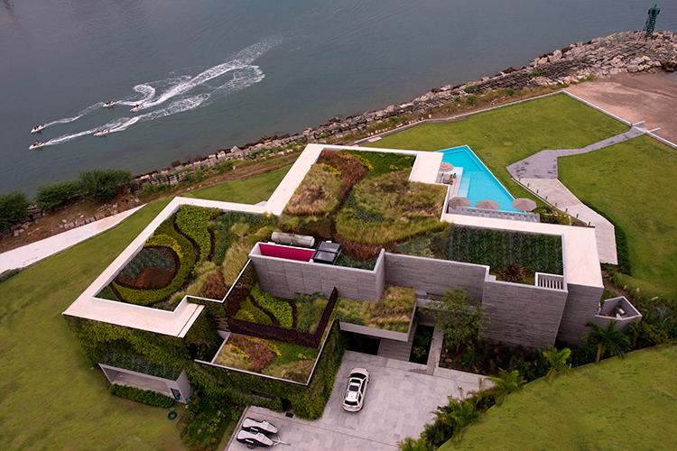 Casa à beira-mar destaca-se por sua cobertura verde